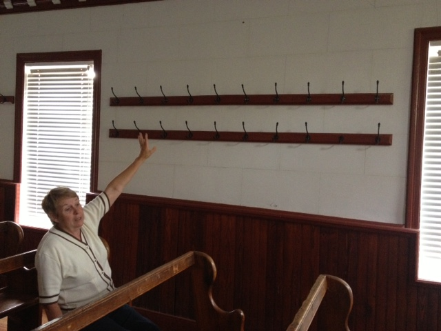 Yvonne sitting in her family pew at Nazareth Chapel pointing out the hooks where her relatives would hang their Sunday coats.